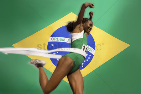 Proud : Runner breaking through the finishing line tape over brazilian flag