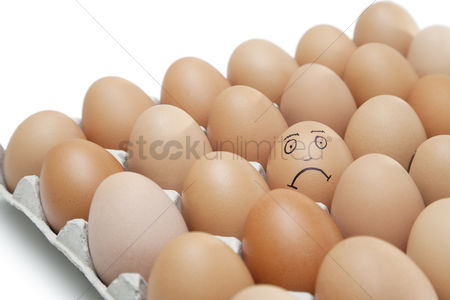 Egg tray : Sad face drawn on an egg surrounded by plain brown eggs in carton against white background