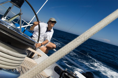 Rope : Sailor at helm of yacht on ocean