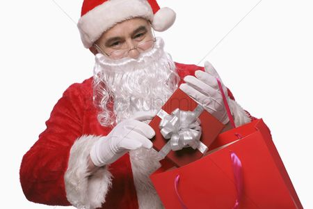 Shopping background : Santa claus putting gift box into shopping bag