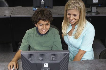 Teacher : School boy using computer with teacher in classroom