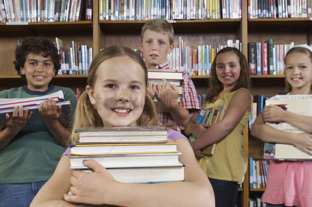 Pupil : School children holding books in library portrait
