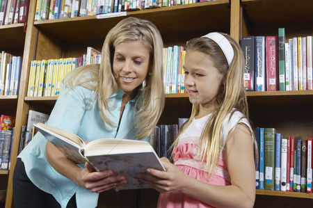 Pupil : School girl reading book with teacher in library
