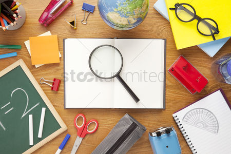 Magnifying glass : School supplies on desk background with copy space