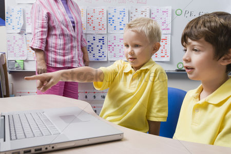Young boy : Schoolboy pointing at a laptop