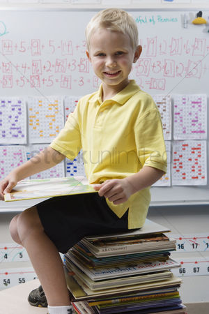 Young boy : Schoolboy sitting on a stack of books