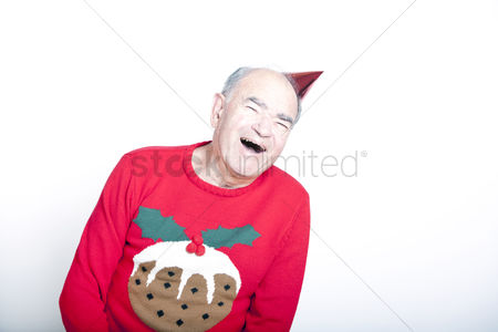 Funny : Senior adult man wearing a christmas jumper and a red party hat
