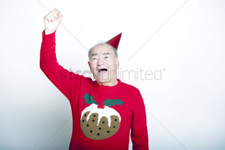 Funny : Senior adult man wearing christmas jumper raising his arm in the air
