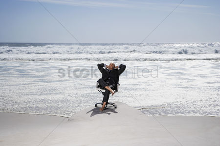 Business suit : Senior business man sitting on office chair on beach elevated view