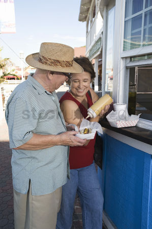 Hot dog : Senior couple buying hot dogs at food stand