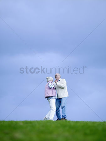 Dancing : Senior couple embracing outdoors  low angle view