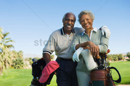 Sports : Senior couple in golf course smiling  portrait