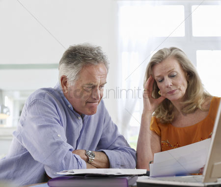 Two people : Senior couple looking at bills sitting at dining table