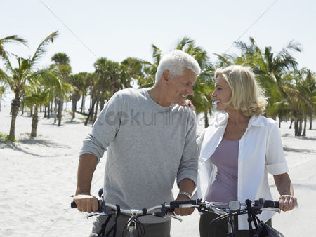 Retirement : Senior couple on bicycles on tropical beach
