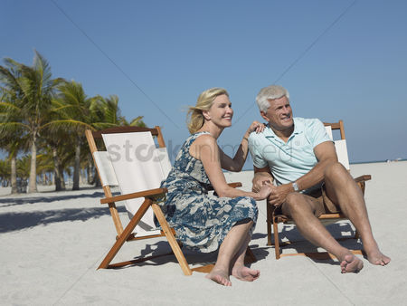 Relationships : Senior couple on sunloungers on tropical beach