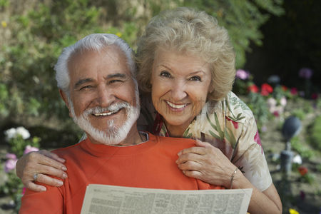 Two people : Senior couple reading newspaper in garden portrait