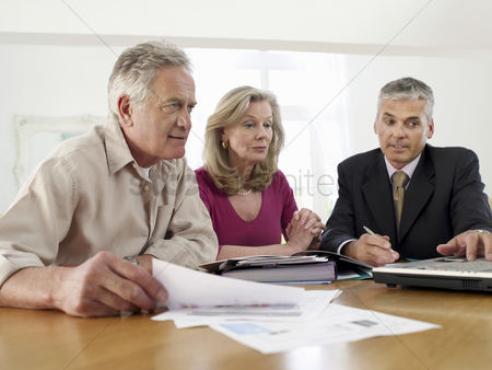 Business suit : Senior couple sitting at table with financial advisor