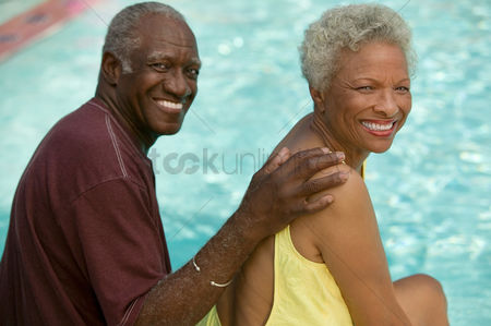 Smiling : Senior couple sitting by swimming pool portrait