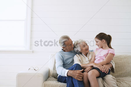 Sitting on lap : Senior couple sitting with daughter on couch