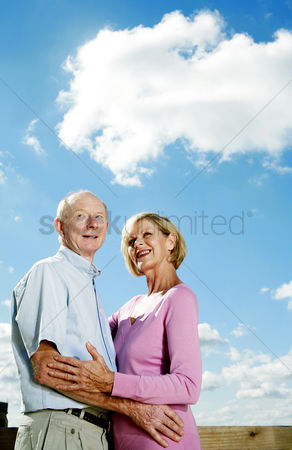 Aging process : Senior couple smiling while hugging