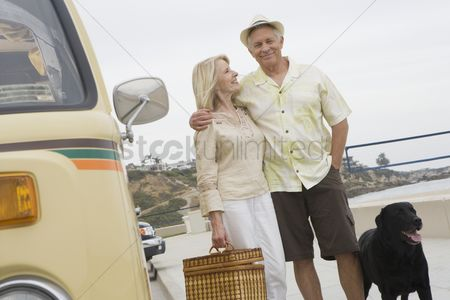 Pocket : Senior couple stand on beach promenade with campervan