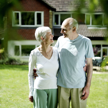 Satisfaction : Senior couple standing in front of their house