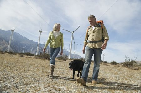 Senior women : Senior couple walking with dog near wind farm