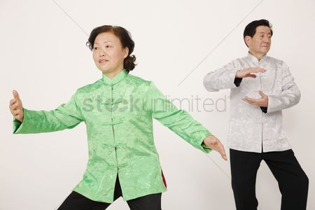 Traditional clothing : Senior man and woman doing tai chi