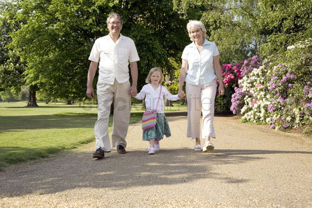Seniors : Senior man and woman walking in the park with a girl