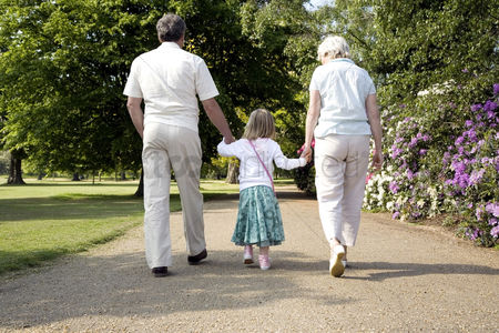 Retirement : Senior man and woman walking in the park with a girl