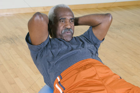 Posed : Senior man doing sit-ups on exercise ball