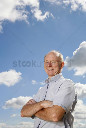 Aging process : Senior man folding his arms while smiling at the camera