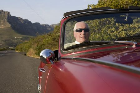 On the road : Senior man in vintage racing car on signal hill  cape town  south africa