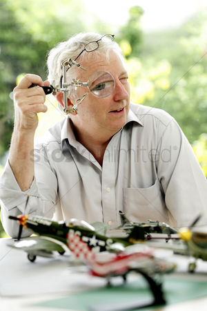 Fixing : Senior man looking through a magnifying glass