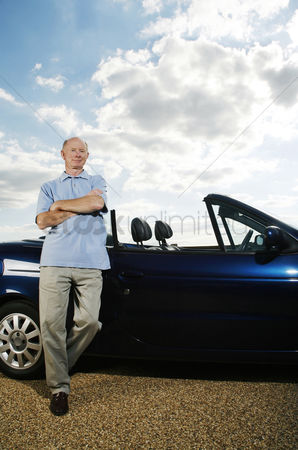 On the road : Senior man posing beside his car