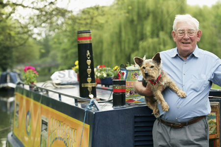 Houseboat : Senior man posing with his dog on houseboat