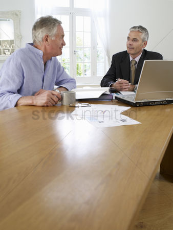 Sitting on lap : Senior man sitting at table with financial advisor