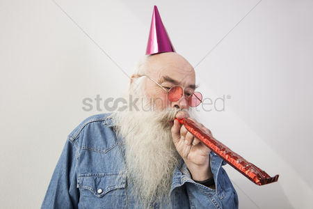 Celebrating : Senior man wearing party hat while blowing horn against gray background