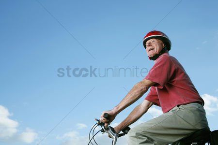 Transportation : Senior man with helmet riding on bicycle