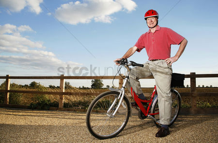 Aging process : Senior man with safety helmet sitting on a bicycle