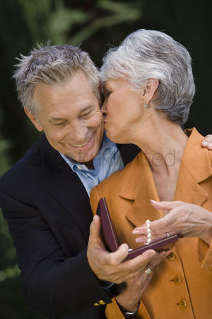 Kissing : Senior man with senior woman holding pearl necklace