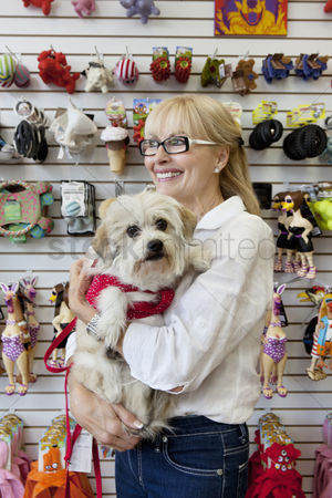 Domesticated animal : Senior pet shop owner standing with dog