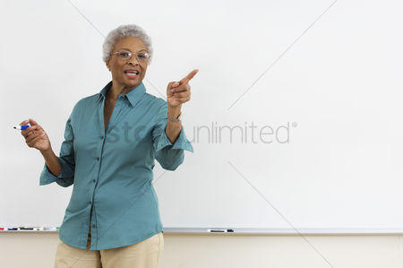 Three quarter length : Senior teacher pointing while gesturing against white board in classroom