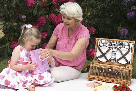 Birthday present : Senior woman and girl picnicking in the park