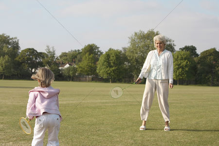 Children playing : Senior woman and girl playing badminton