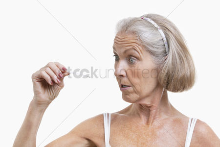 Thermometer : Senior woman checking thermometer against white background