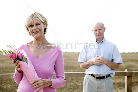 Satisfaction : Senior woman holding a bouquet of flowers with her husband standing behind her