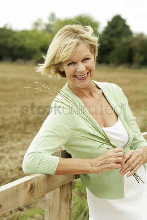 Resting : Senior woman holding a wheat grass while smiling at the camera