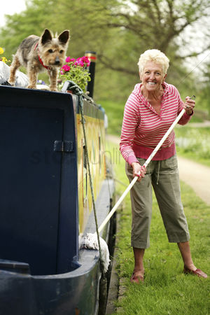 Aging process : Senior woman mopping houseboat