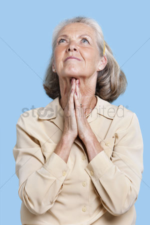Religion : Senior woman praying with hands clasped against blue background